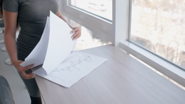 Young sexy businesswoman is analyzing documents standing in office interior.