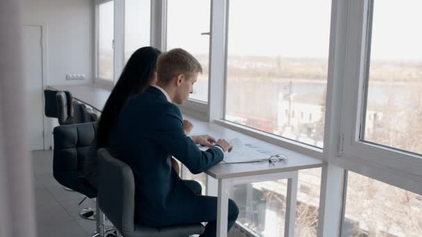 Young businesspeople working on business project sitting by window in modern office.