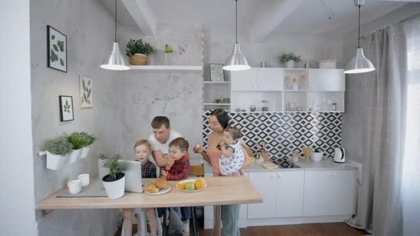 Mnohonárodnostní rodina sleduje kreslené na přenosném počítači, jíst ovoce