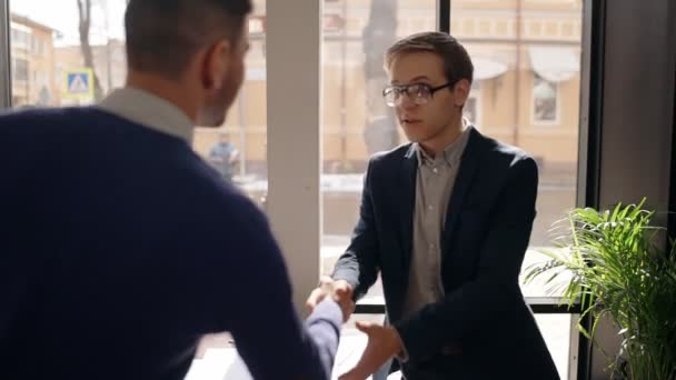 Young businessmen are shaking hands during business meeting in modern cafe.