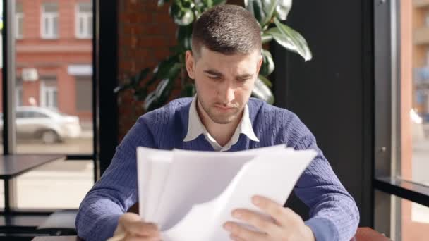 Young successful businessman is reading contract, sitting at table in cafe.