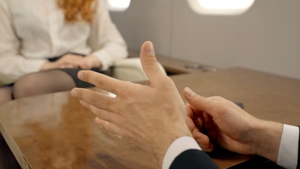 Young successful businesspeople are communicating, sitting at table in private plane.