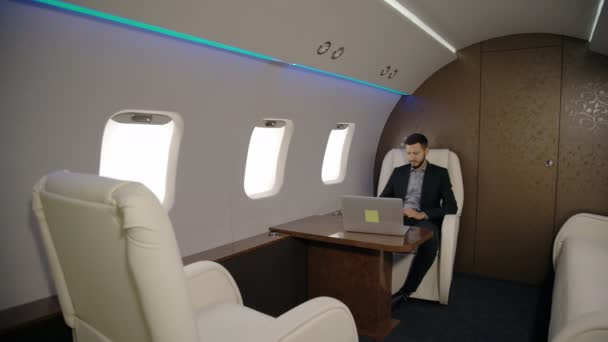 Young stylish lawyer entrepreneur businessman is using laptop sitting in airplane interior.