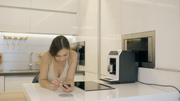 Krásná žena, psaní zpráv na svém smartphonu v interiéru moderní kuchyně