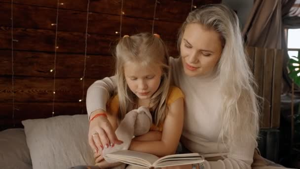 Very beautiful mother read wonderful fairytales to little charming girl.