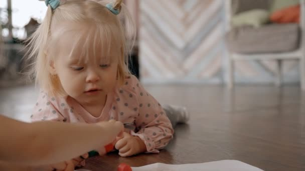 Little pretty girl with sweet pony tails is learning and practicing to draw by crayons.