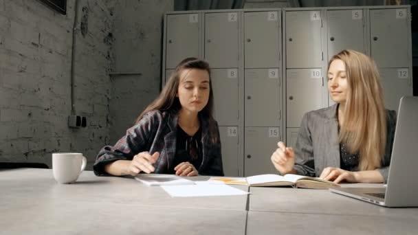 Due colleghe collaborando nel loft spazio di coworking. Designer e imprenditrice condivisione idee nello sviluppo di business, utilizzando computer notebook e portatili