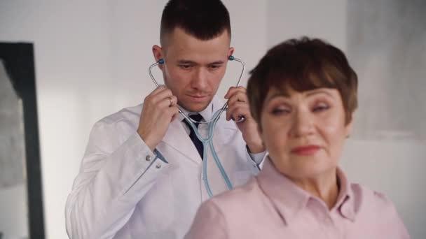 Lékařka inteligentní specialista a praktický lékař zkoumá staršího pacienta