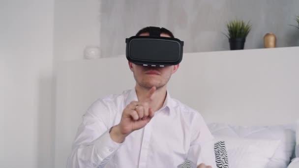 Mann sitzt auf weißem Sofa mit digitaler Technologie der erweiterten Realität
