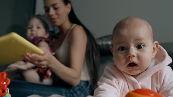 Mladá Američanka a dvě děti sedící na pohovce v pokoji.