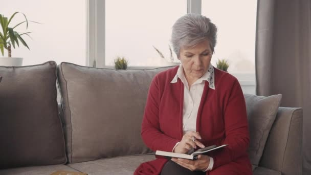 Senior woman is sitting on couch and writing new important information