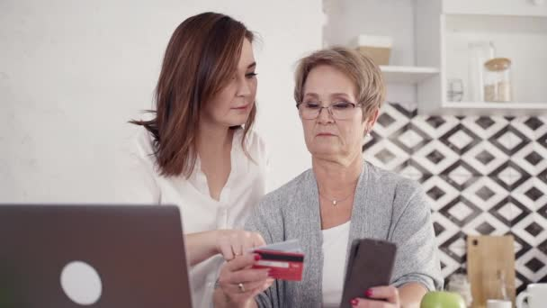 Daughter helping her senior mother making online shopping with s