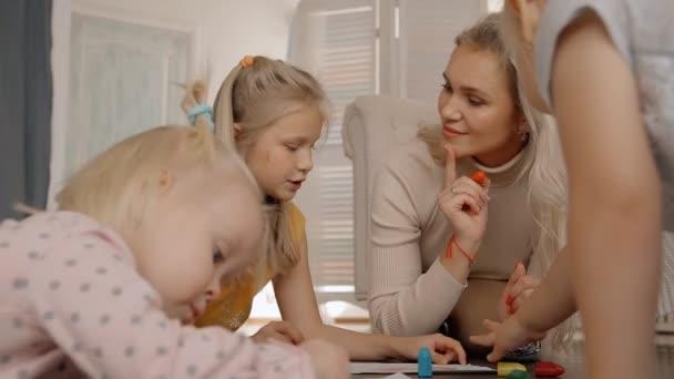 Žena mluví a kreslí s dětmi v moderním interiéru místnosti