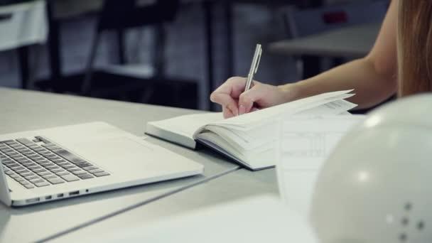 junge Frau zeigt Informationen über letztes Marketingprojekt in Notizbuch.
