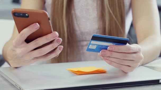 Fiatal nő kezében műanyag kártya és okos telefon a kezében