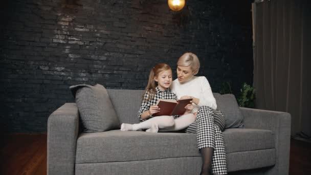 Kavkazská matka učí chytré dívky číst knihu nahlas s výrazem.