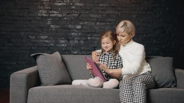 Samice používající digitální tablet s malým krásným dítětem