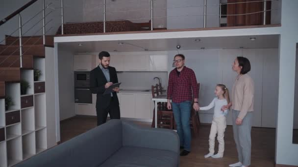 Husband, wife and daughter standing inside flat while real estat