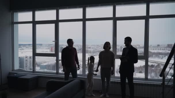 Magabiztos ingatlanközvetítő mutatja az új házat, hogy boldog család