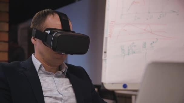 Mann trägt Virtual-Reality-Brille und sitzt im Büro