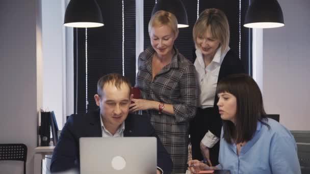Dospělý muž a žena používající přenosný počítač a zobrazující displej