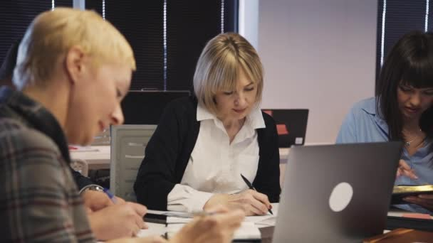 Ženská tvorba poznámek a plánování nové strategie společně v kanceláři