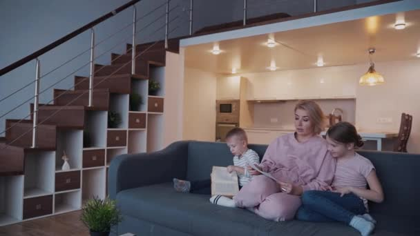 Woman hold daughter draw in hands while her son play with book