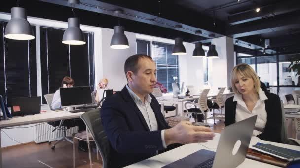 Muž a žena, kteří plánují nový projekt nebo strategii a používají přenosný počítač