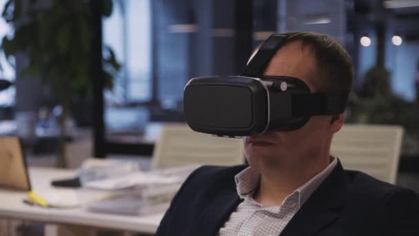 Mann trägt 3D-Helm oder Brille und arbeitet im virtuellen Raum