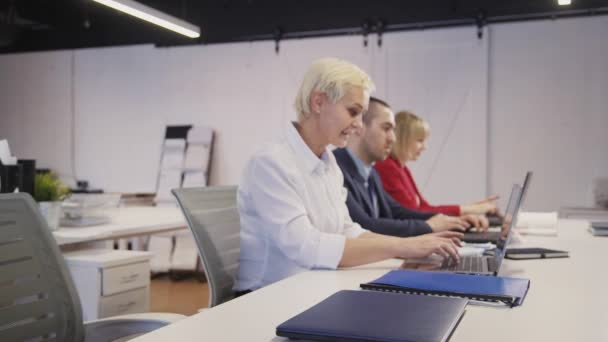 Man using laptop in office against backgrounds with colleagues