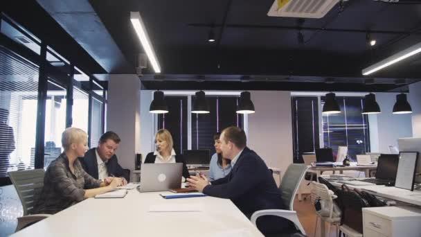 Žena a muž, kteří si povídají, dělají poznámky, používají přenosný počítač a pracují v