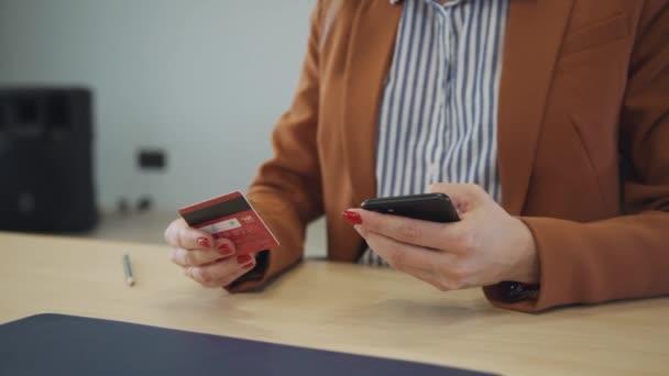 Magabiztos üzletasszony Holding kártya és smartphone-ban odaad ülő-ban asztal-ban szoba.