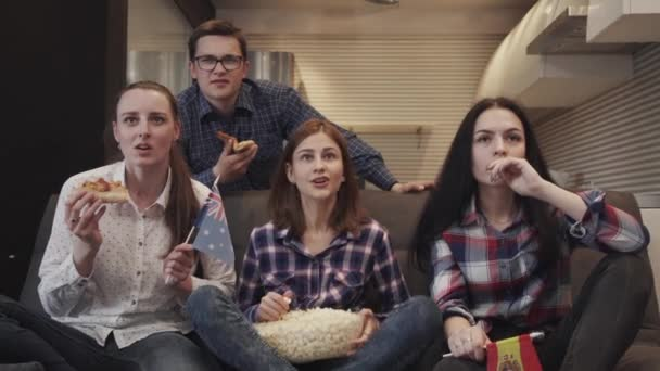 Four friends sitting on couch together and watching tv