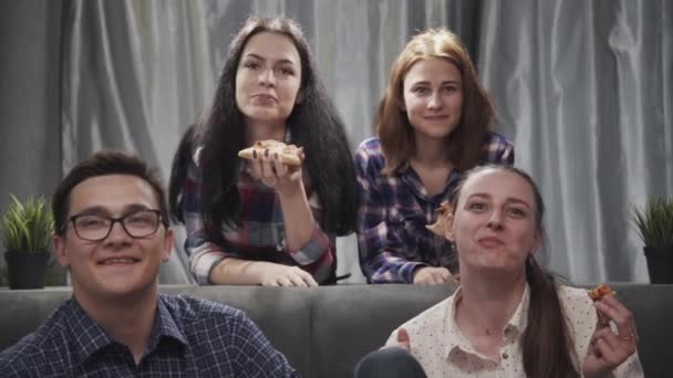 Four people sitting on couch, watching tv
