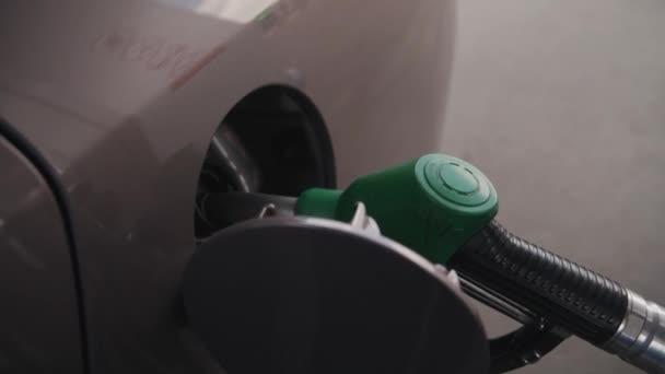 Benzínová pistole vložená do palivové nádrže, plnící auto na ulici.