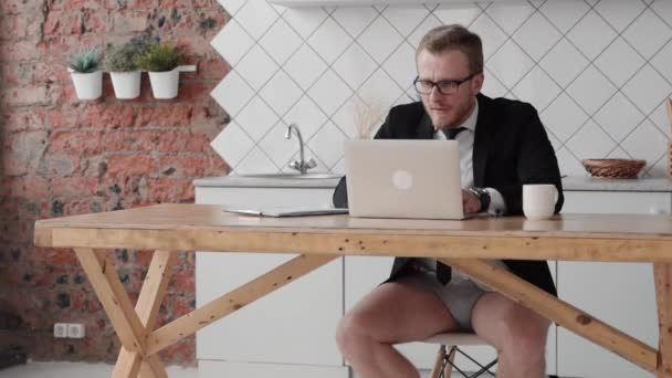 Young american man is working with laptop sitting at table in home kitchen.