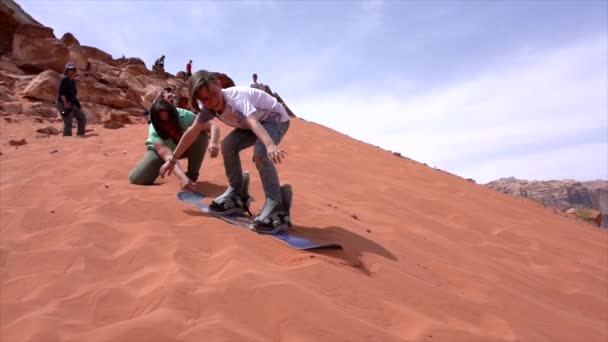 wadi rum, jordan - 2019-04-23 - Junge versucht, Sanddüne mit dem Snowboard hinunter zu brettern, findet sie aber zu klebrig