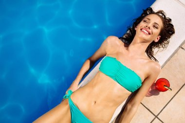 Woman sunbathing at swimming pool during summer