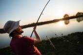Fotografie Mladý muž rybolov na rybníku a těší hobby