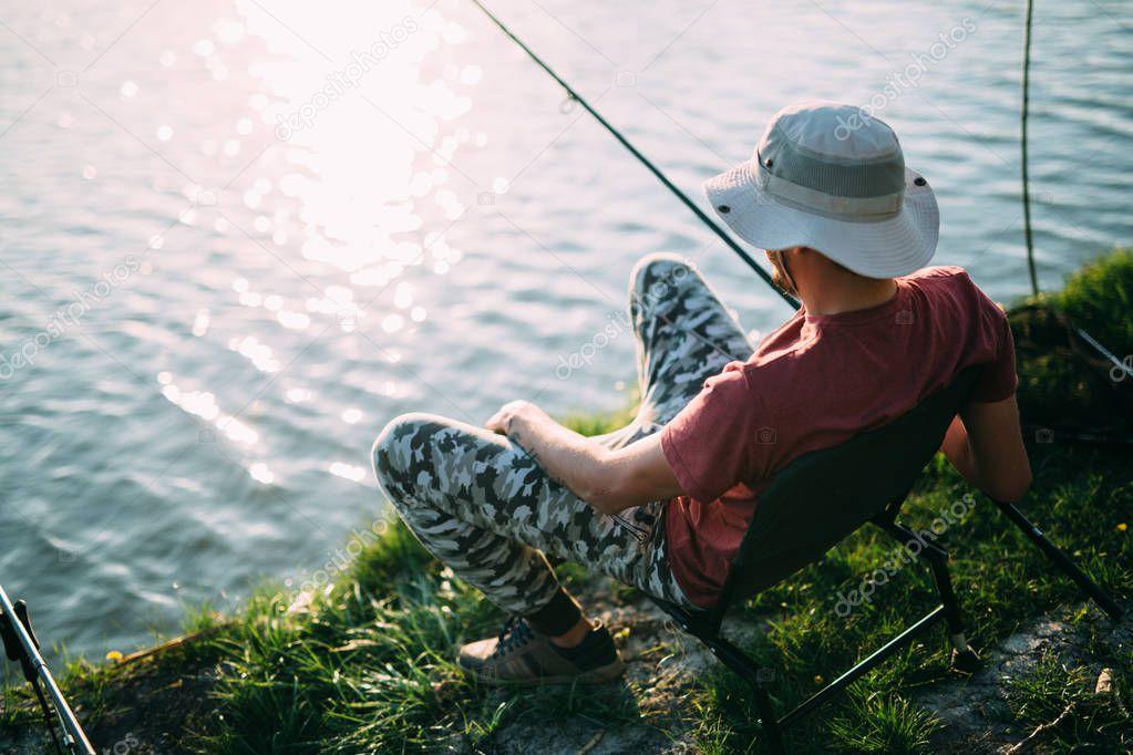 Young man fishing at pond and enjoying hobby