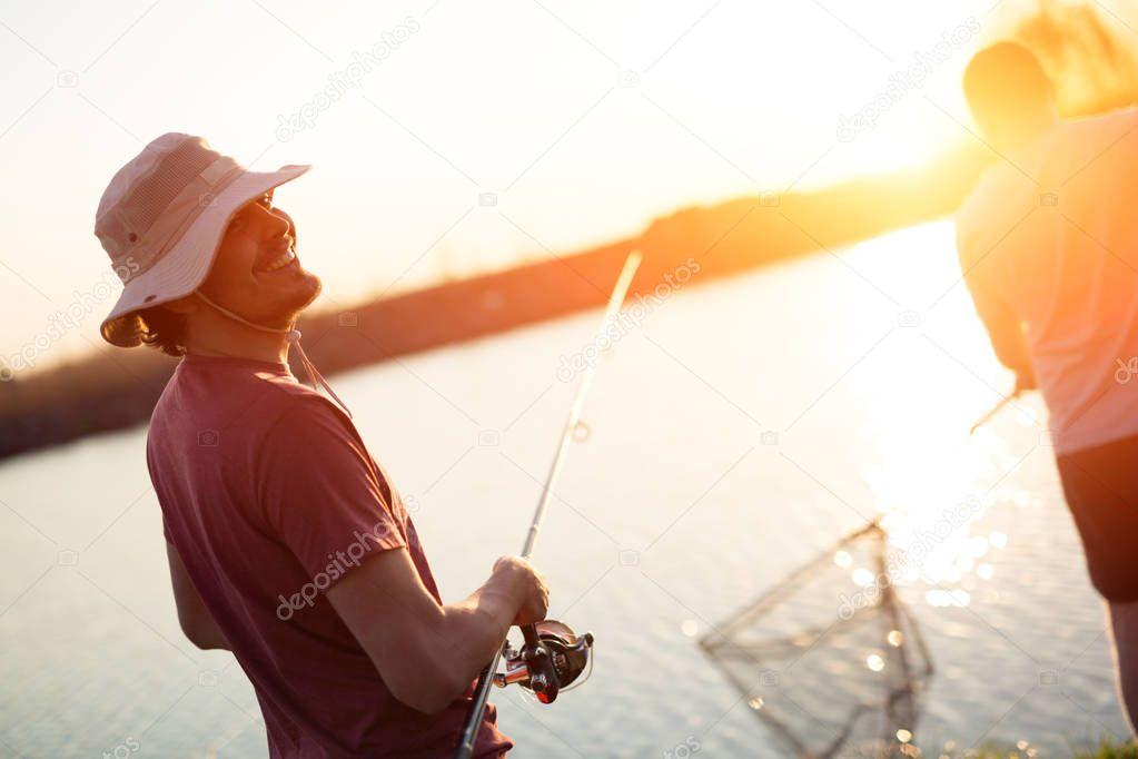Men fishing in sunset