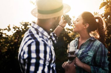 Couple in love working at winemaker vineyard and tasting wines