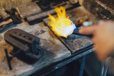 Jeweler welding gold, metal the traditional way