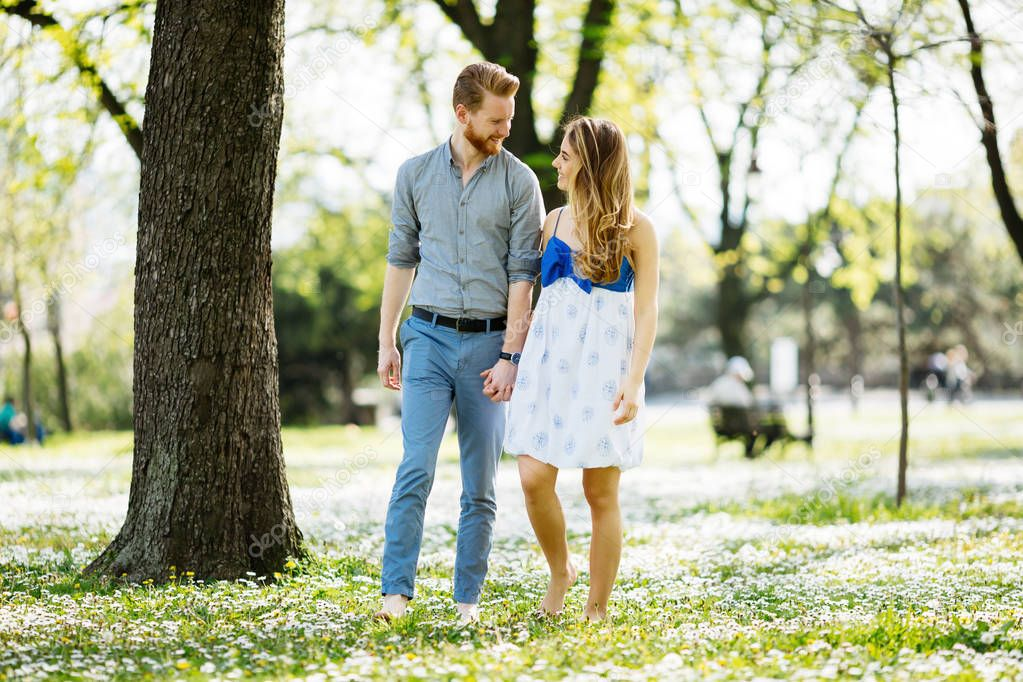 Beautiful couple in park taking a walk barefoot