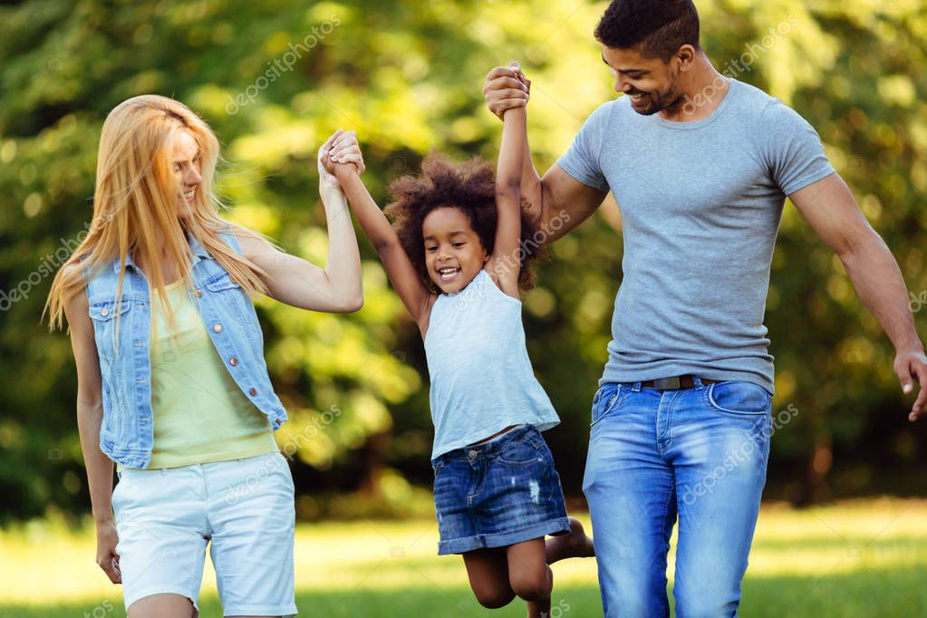 Happy young couple spending time with their daughter in nature
