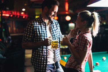 Young attractive couple together on date in snooker club