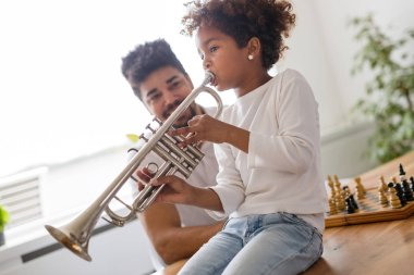 Cute girl with her father learning trumpet