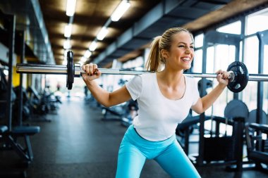 Beautiful active woman doing squats with weights in gym