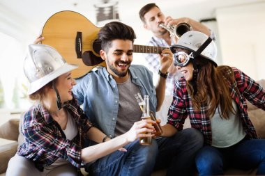Cheerful young friends having party together and playing instruments