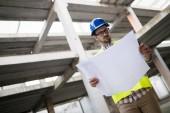 Porträt eines männlichen Bauunternehmers mit Hut, der blaues Druckpapier auf der Baustelle hält,
